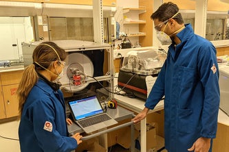 Graduate students Esther Monroe (left) and Nishit Shetty carry out droplet experiments using a custom-built environmental rotating chamber. A team of researchers at Washington University in St. Louis are developing devices to detect the virus that causes COVID-19 in the air.