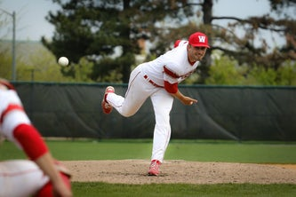 Loutos throws a warmup pitch during a game against Spalding University in April. (Photo by Clara Richards | Student Life)